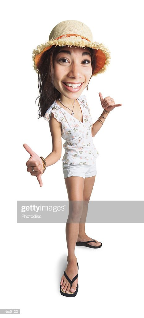 a young ethnic female wearing a straw hat holds out her hands to make the hang loose sign : Foto de stock