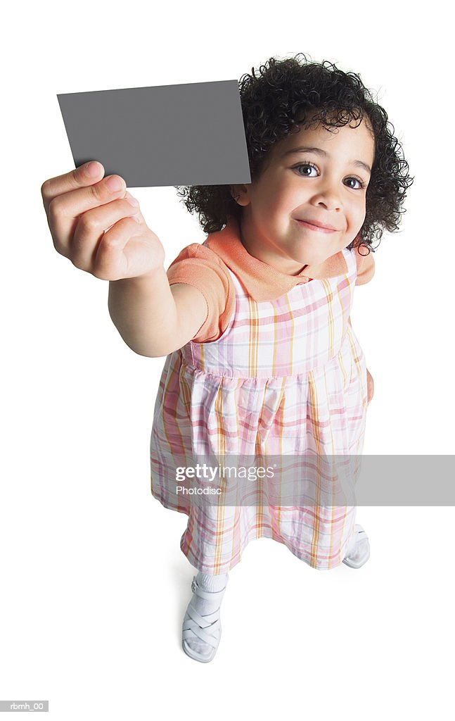 a young ethnic girl in a pastel dress holds a blank sign up to the side of her head and smiles : Stockfoto