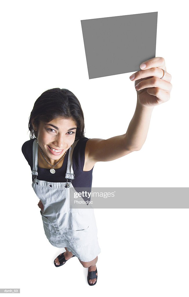 a young ethnic girl wearing a kahki overall dress and a black shirt holds a small blank sign up with one hand as she looks up at the camera : Stockfoto