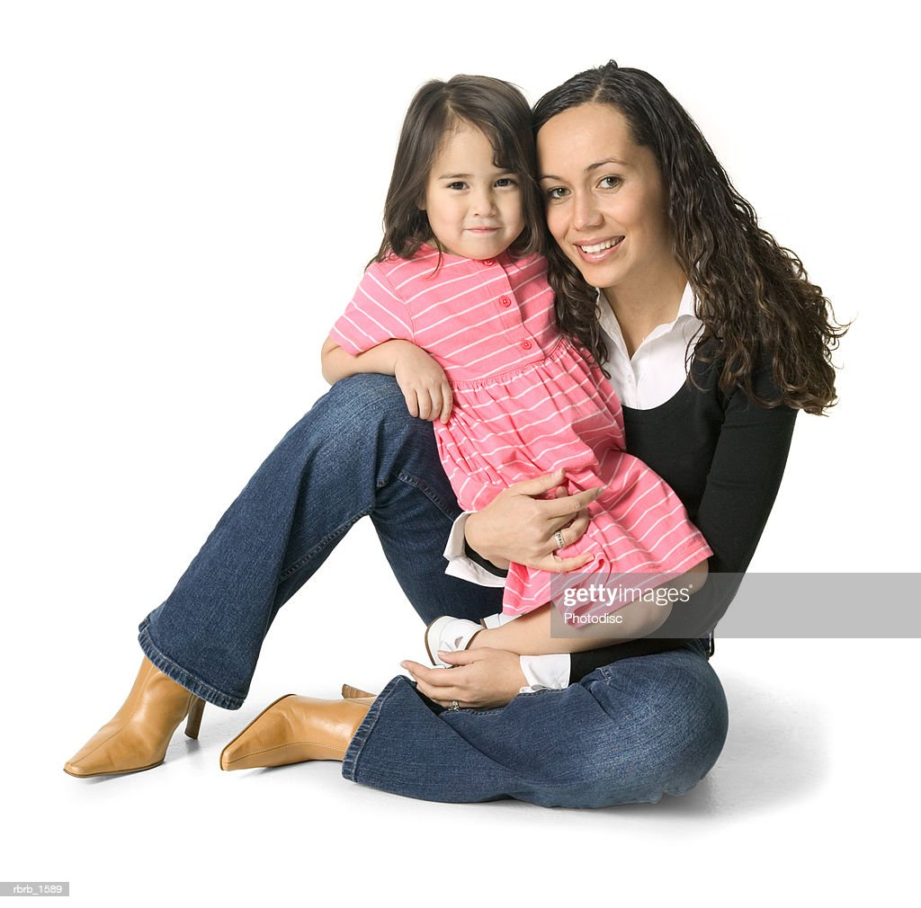 a young ethnic woman sits with her little sister on her lap : Stockfoto