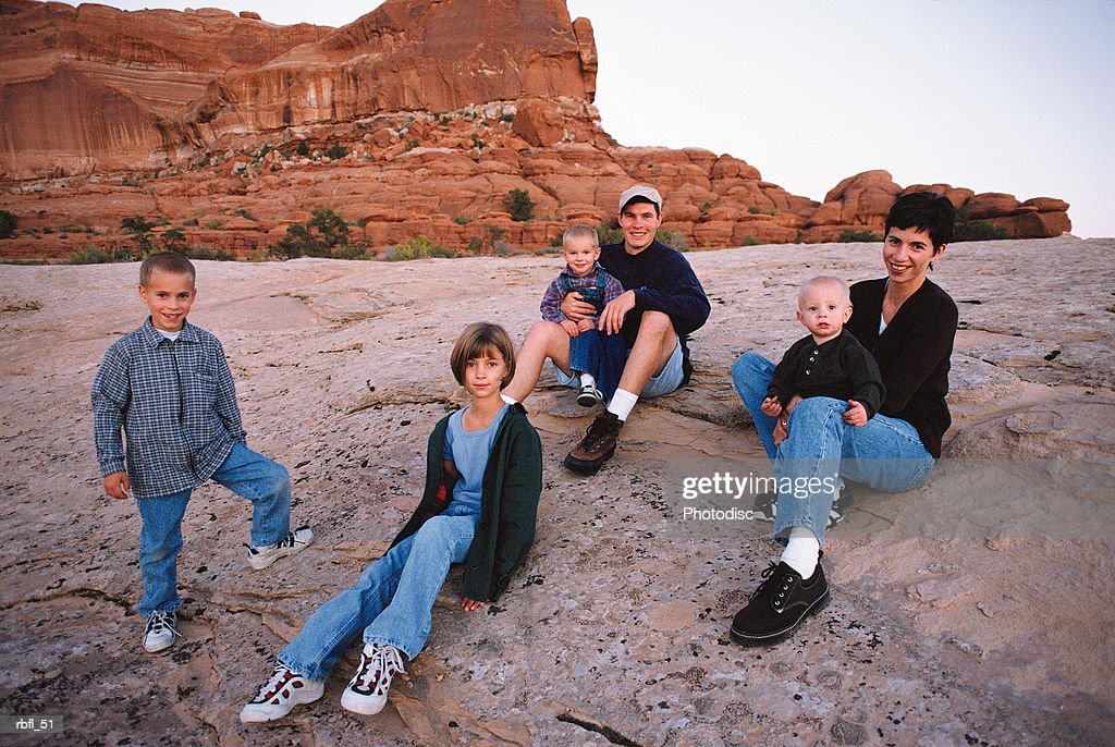 a young family rests disjointedly on a rock bed : Stockfoto
