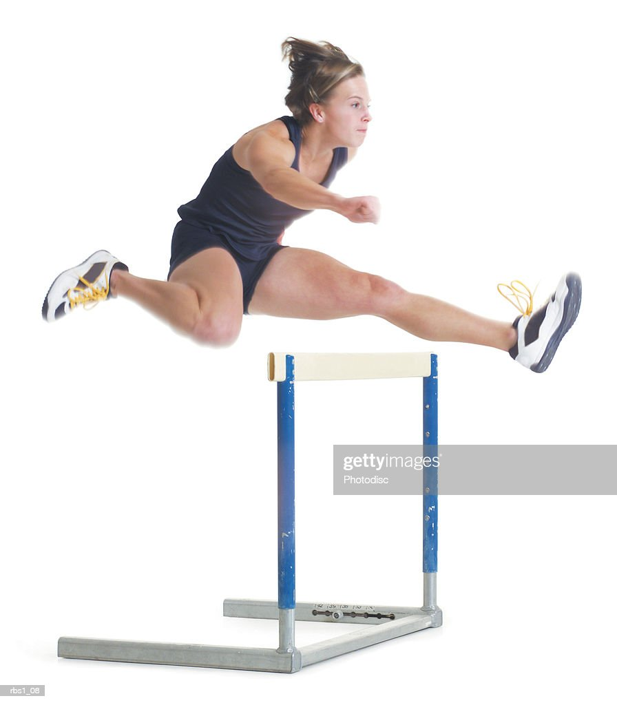 a young female caucasain runner wearing a black uniform is jumping over a hurdle : Foto de stock