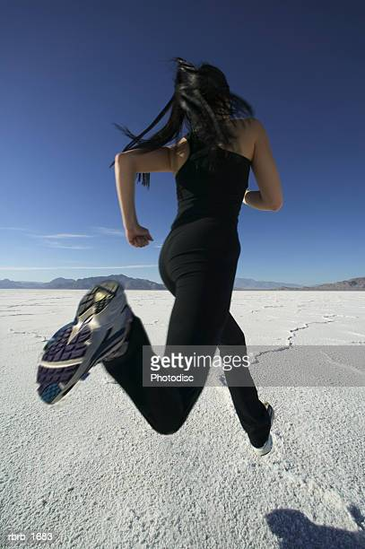 a young female jogger in a black workout outfit runs through a vast open desert