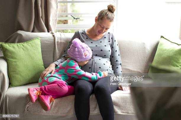a Young girl bonding with her mother's unborn baby.