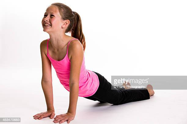 a young girl in black pants and pink top does yoga