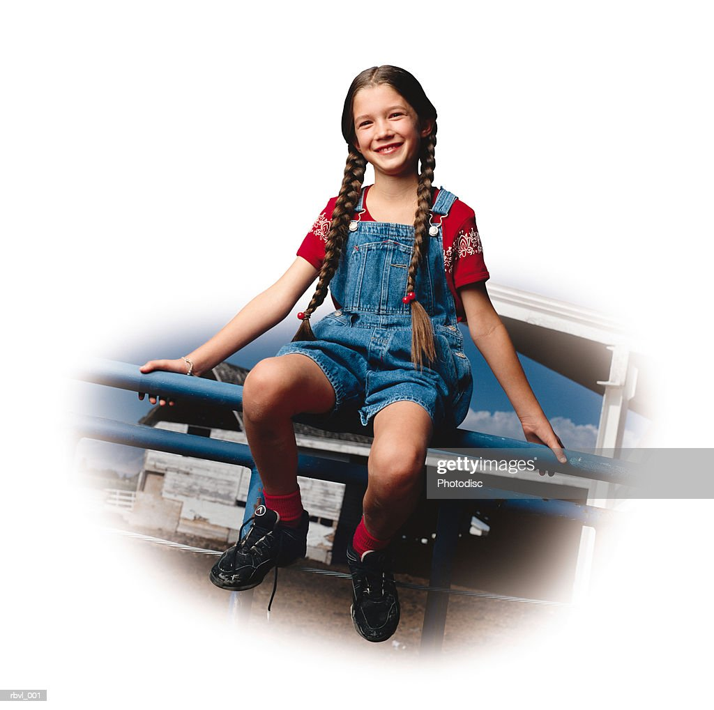 a young girl in jean overalls and red shirt with long braids sits on a fence smiling at the camera : Foto de stock