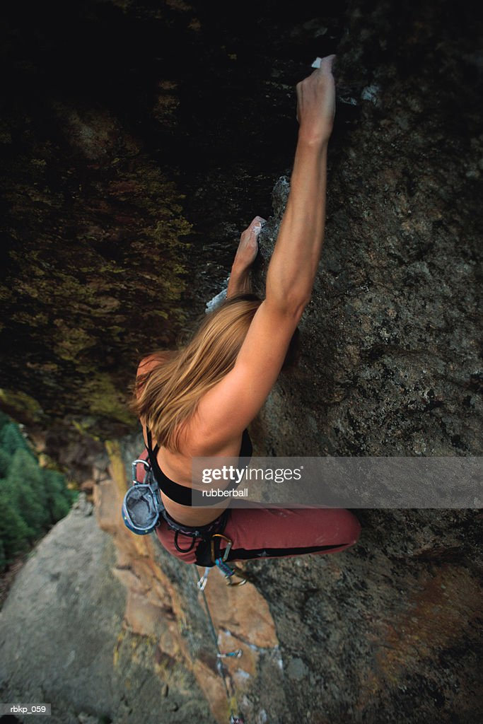 a young girl is hanging from large grey cliff that she is climbing with the ground in view below her some several hundred feet : Stockfoto