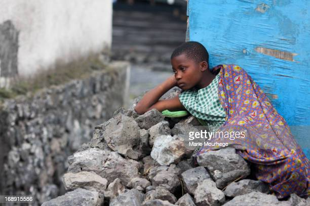 CONTENT] a young girl refugee from Rwanda resting on a pile of rocks in a medical center in Goma the Democratic Republic of Conga waiting to receive...