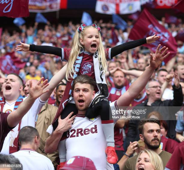 a young girl sits high on the shoulders of an adult Aston Villa supporter during the Sky Bet Championship Playoff Final match between Aston Villa and...