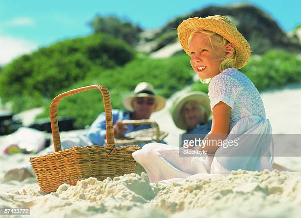 a young girl sitting on beach in front of picnic basket