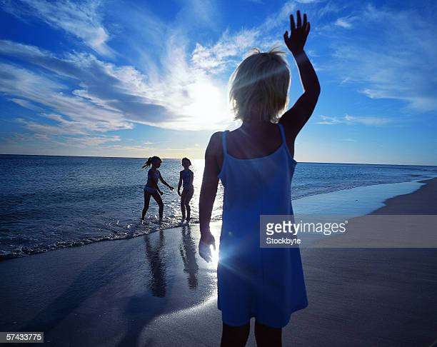 a young girl (7-8) waving to two young girls on the beach