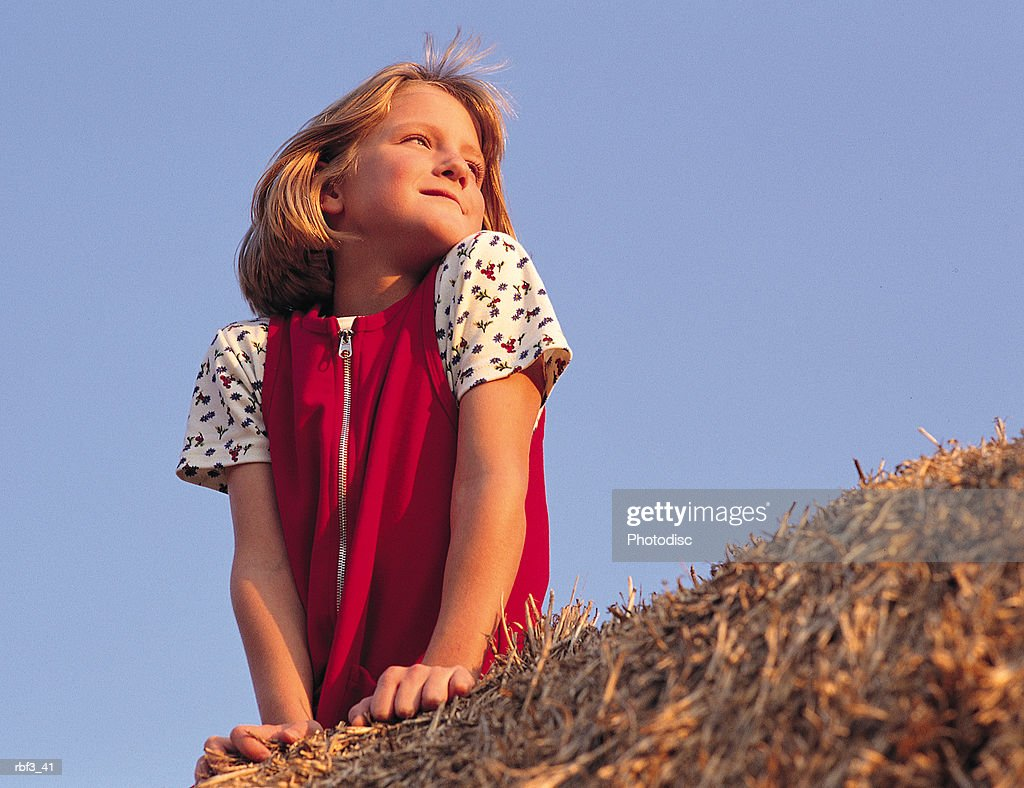 a young girl wearing a red dress sits on top of a bale of hay under a blue sky as she looks over her shoulder into the distance : Stockfoto
