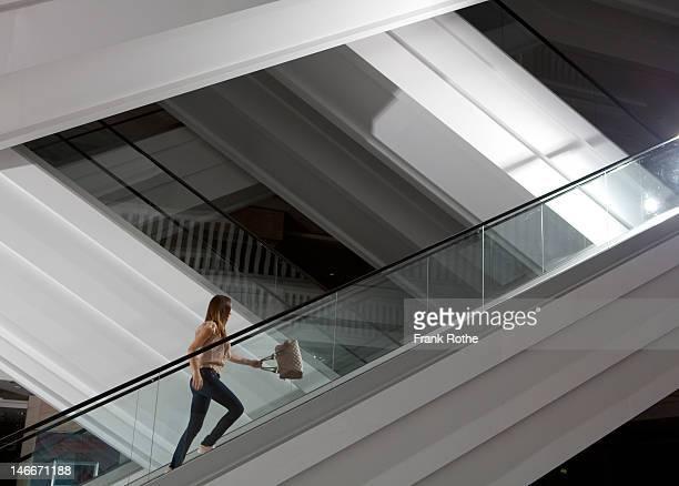 a young girl with a handbag runs up the escalator - escalator stock pictures, royalty-free photos & images