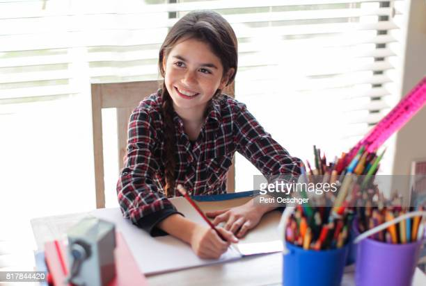 a young girl writing out her homework. - role reversal stock photos and pictures