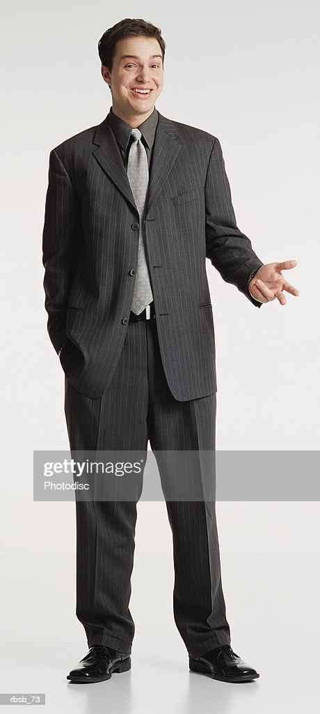 a young handsome caucasian businessman with short dark hair dressed in a dark grey suit looking into the camera with a hand exended in conversational gesture : Stockfoto