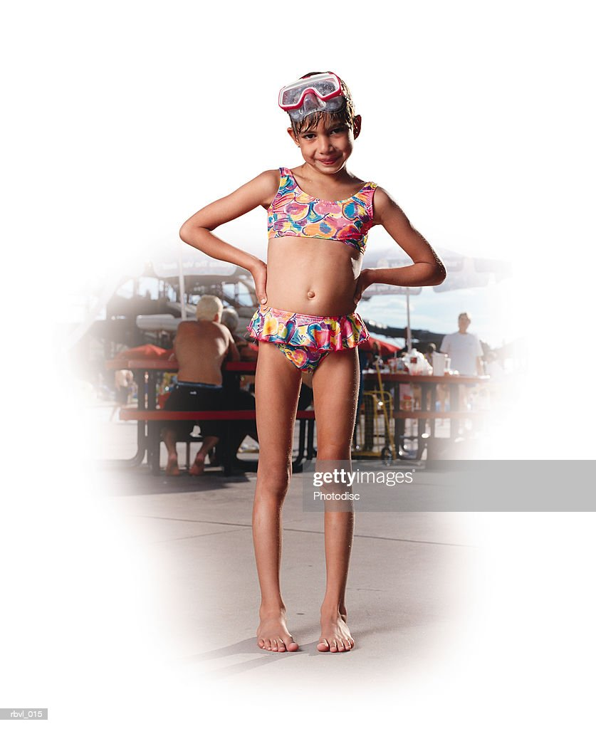 a young hispanic girl is standing with her hands on her hips in a swimming suit and swim mask in front of a water park : Foto de stock