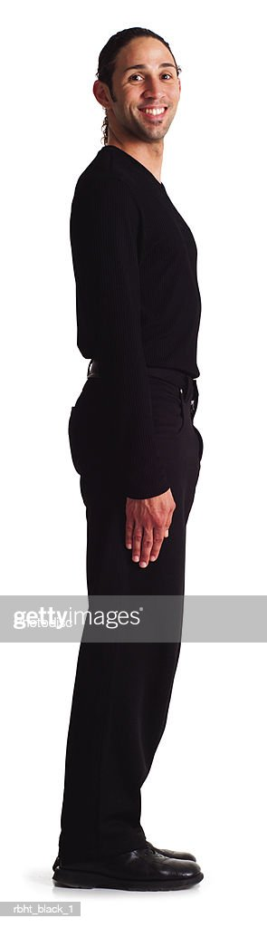 a young hispanic male dressed in black stands in place creating the number one : Stock Photo