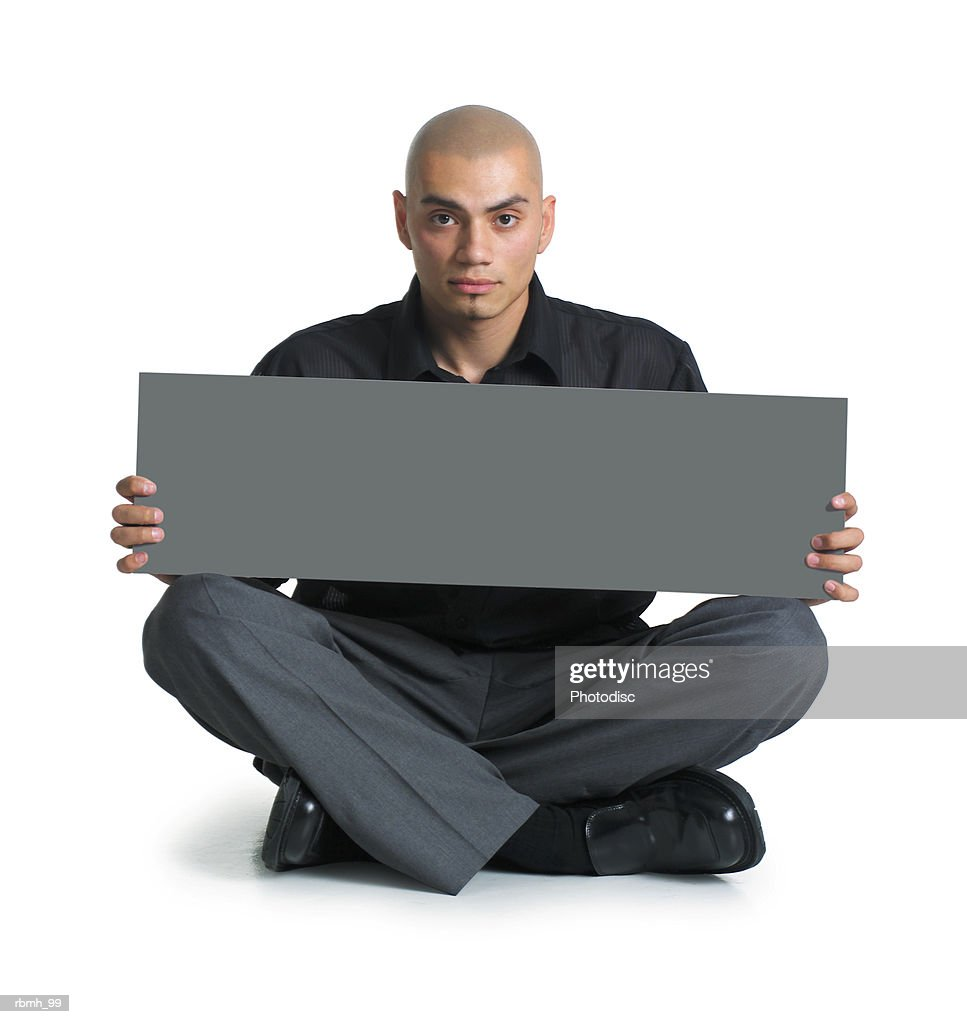 a young hispanic male in grey slacks and a black shirt sits cross-legged on the floor as he holds a blank sign on his lap with both hands and looks straight ahead at the camera : Stockfoto