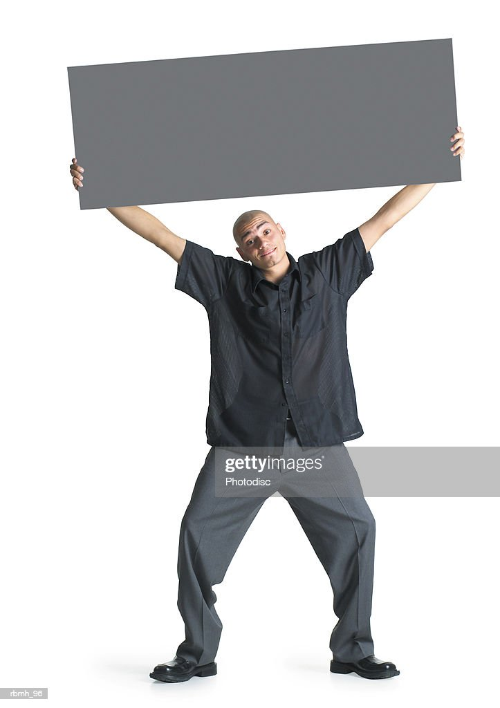 a young hispanic male wearing grey slacks and a black shirt stands with his feet shoulder width apart and his knees bent and head cocked while he spreads his arms overhead to hold a blank sign : Stockfoto