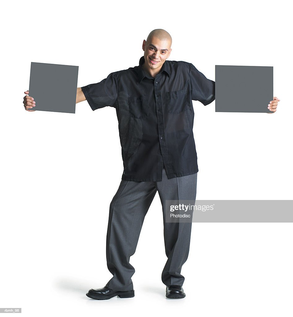 a young hispanic male wearing grey slacks and a black shirt stretches his arms out to hold two blank signs as he smiles at the camera : Stockfoto