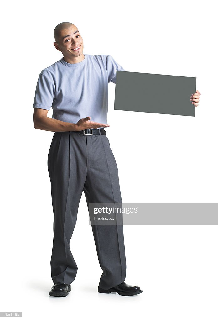 a young hispanic male wearing grey slacks and a blue shirt stands holding a blank sign points to it : Stockfoto