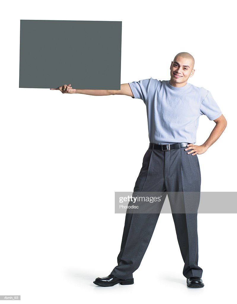 a young hispanic male wearing grey slacks and a blue shirt stands with one hand on his hip and holds out his other arm to hold a blank sign : Stockfoto