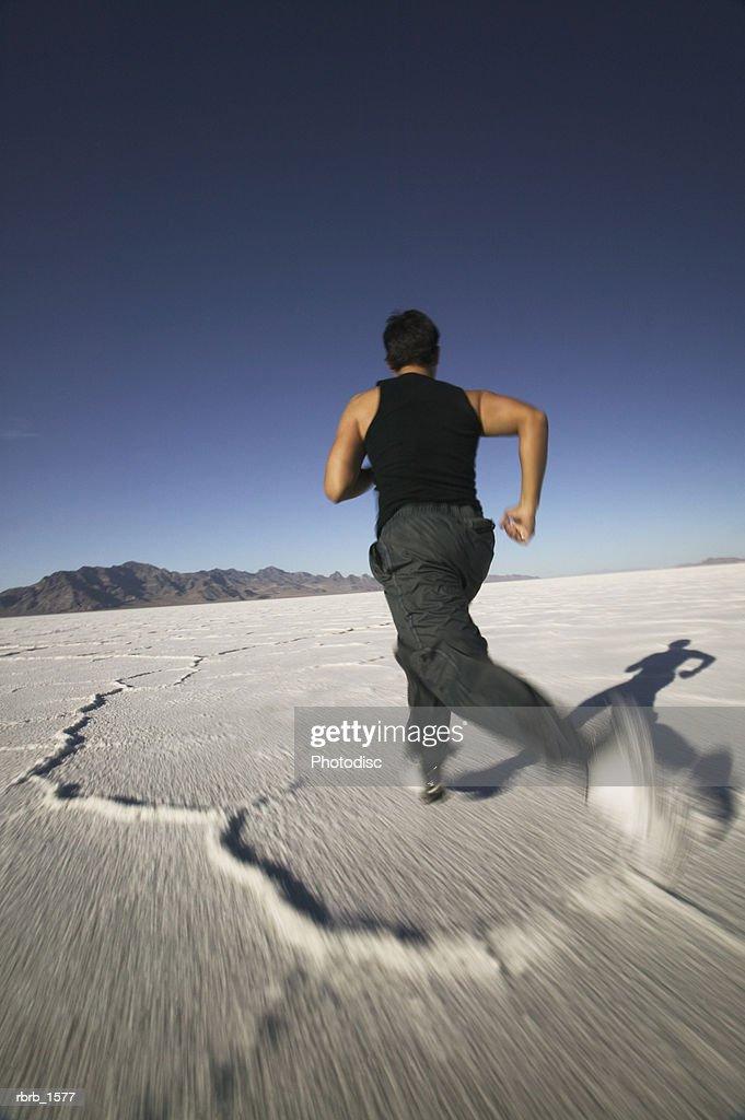 a young hispanic man jogs through the vast open desert : Stockfoto