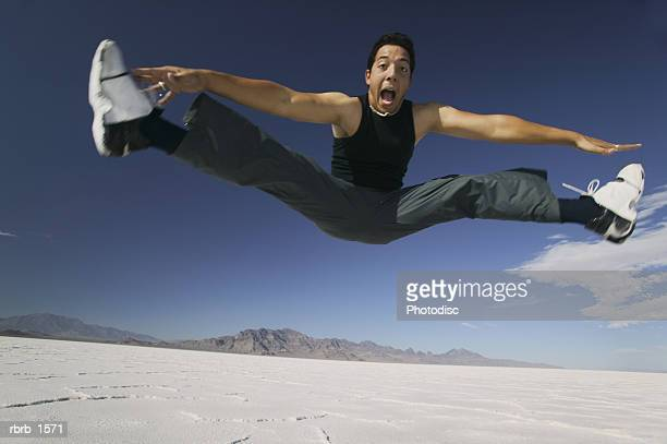 a young hispanic man jumps and does the splits in the the air in a desert setting