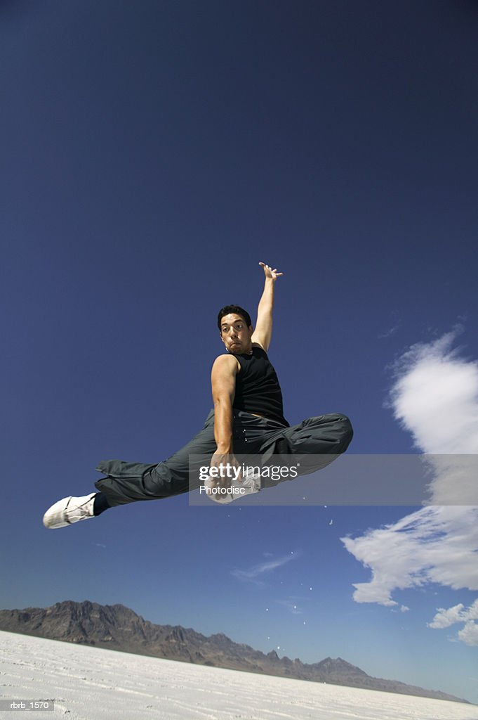 a young hispanic man jumps playfully through the air in the wide open space of a desert : Stockfoto