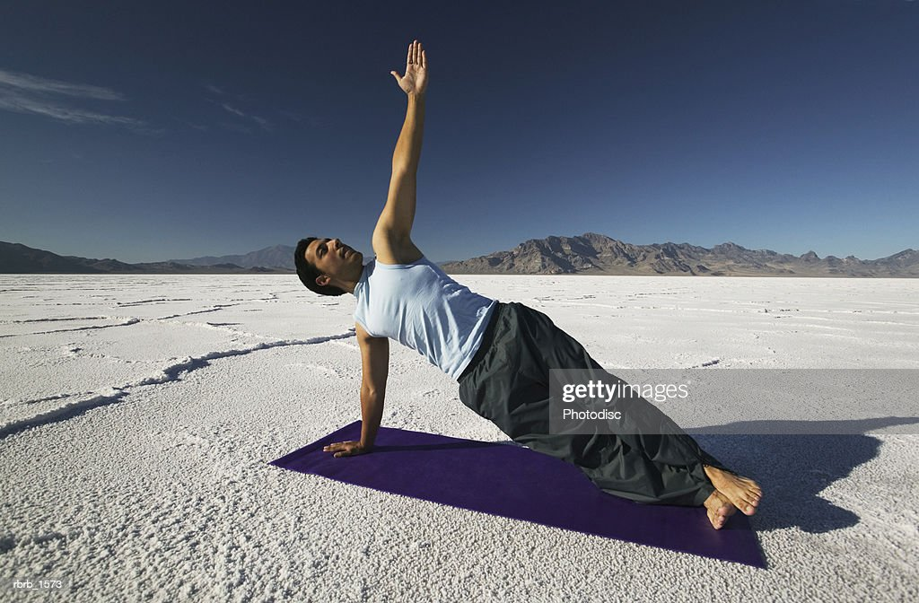 a young hispanic man practices stretching and yoga in a desert setting : Stock Photo