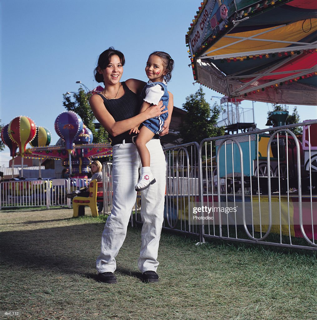 a young hispanic mother in jeans and a tank top holding her little girl with a face painting on her cheek at a fair : Foto de stock