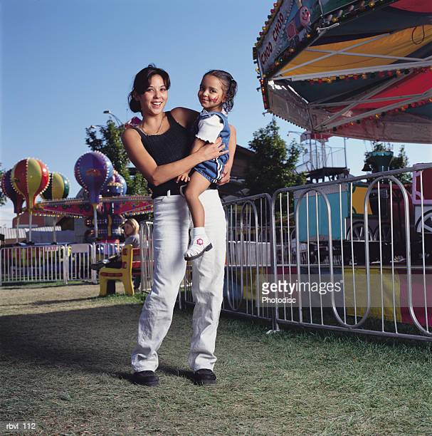 a young hispanic mother in jeans and a tank top holding her little girl with a face painting on her cheek at a fair