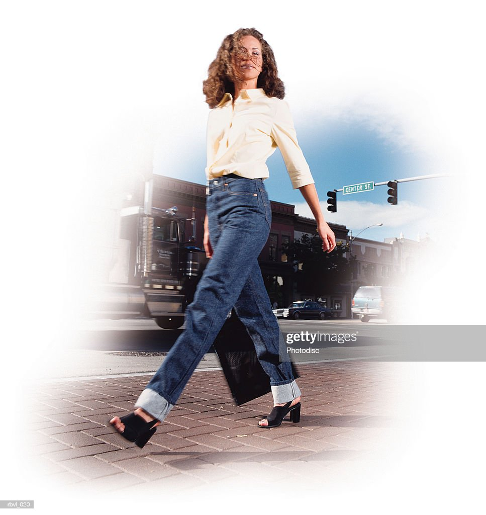 a young hispanic or caucasian woman with curly brown hair in a yellow shirt and blue jeans is walking along a city street : Foto de stock