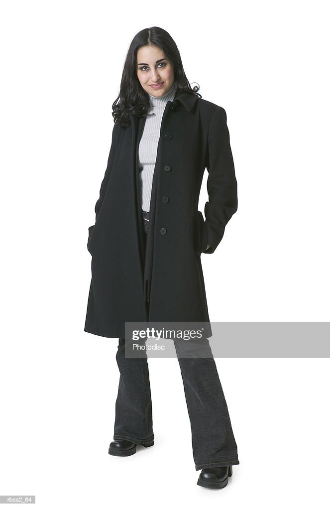 a young hispanic woman in a black coat puts her hands in her pockets and smiles : Foto de stock