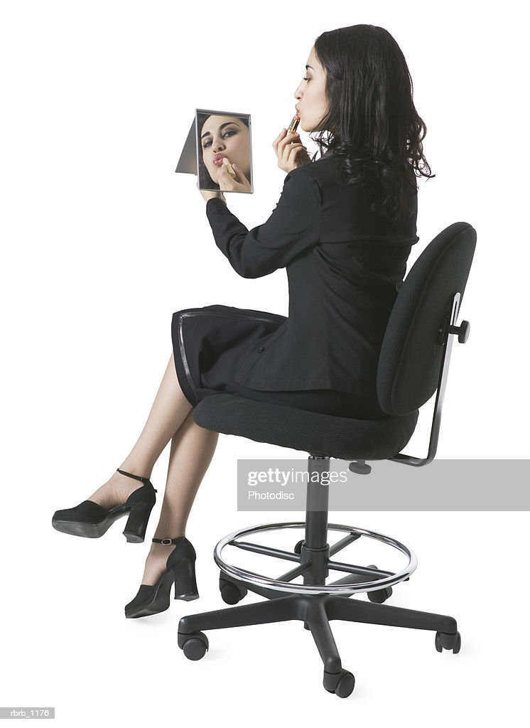 a young hispanic woman in a black suit sits in a chair and looks in a mirror to apply lipstick : Stockfoto