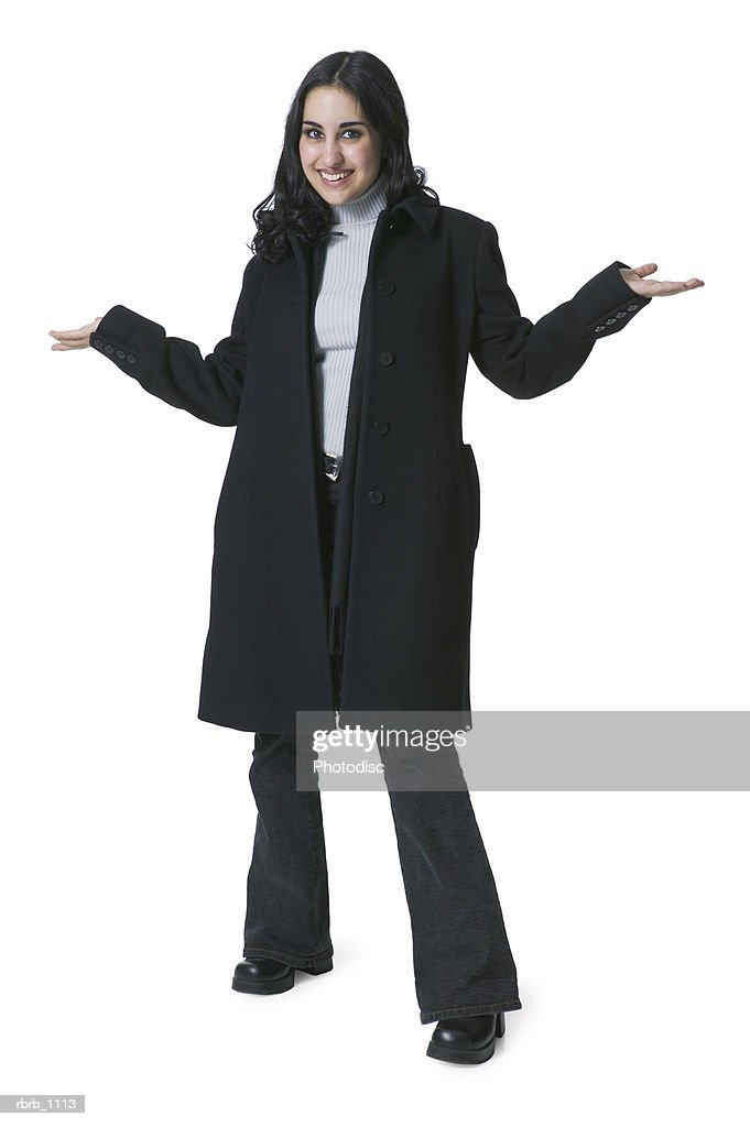 a young hispanic woman in a long black coat smiles as she shrugs her shoulders : Stockfoto