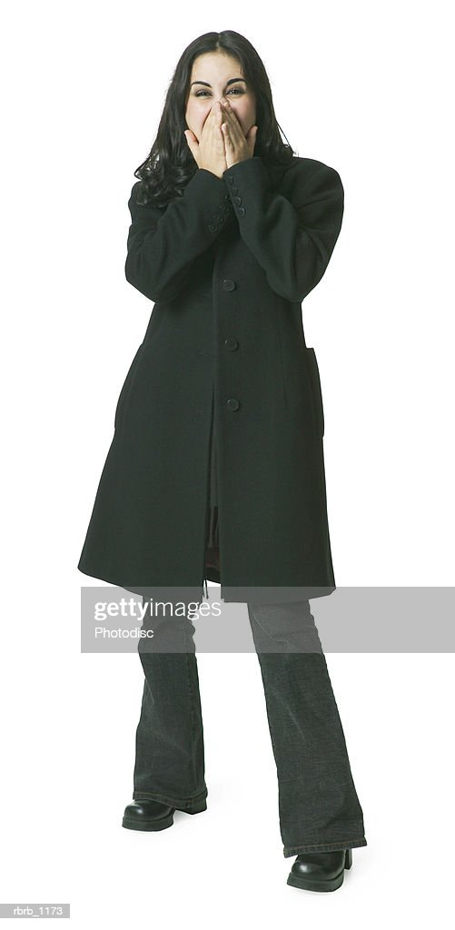 a young hispanic woman in a long dark coat covers her face as if overcome with joy : Stockfoto
