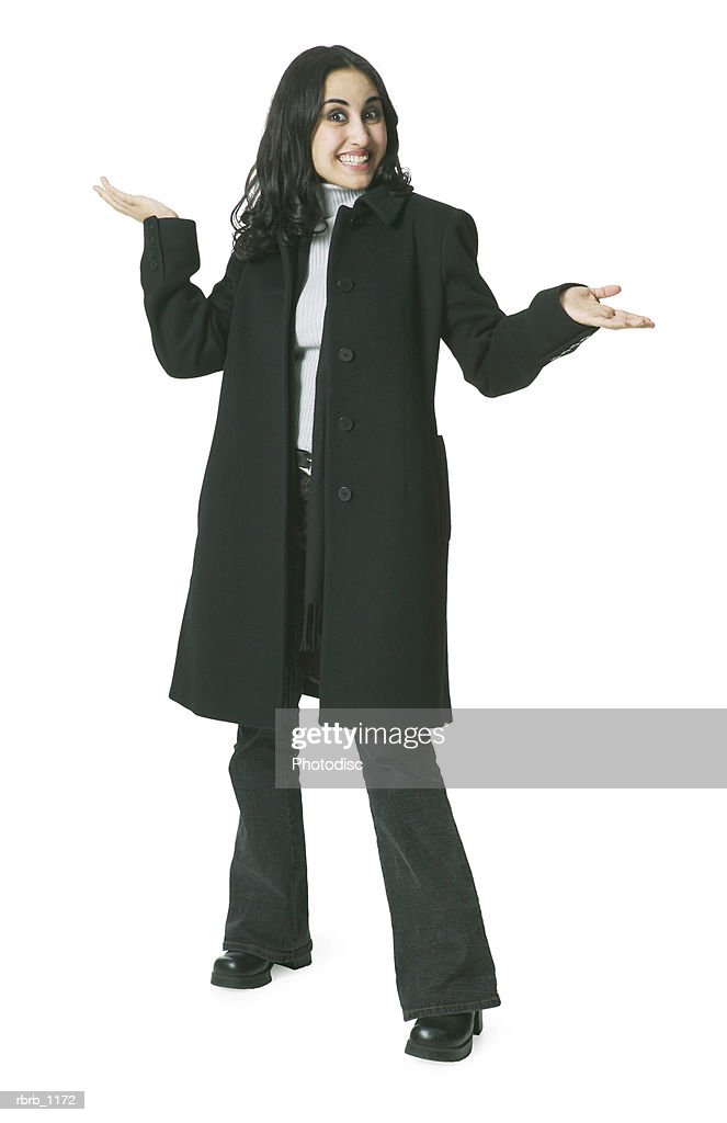 a young hispanic woman in a long dark coat gestures playfully with her hands as she smiles : Stockfoto