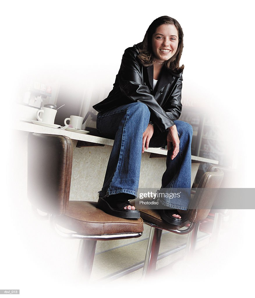 a young hispanic woman in blue jeans and black leather jacket is sittng on the counter of a diner looking into the camera : Foto de stock
