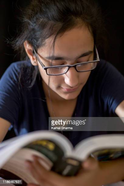 a young indian girl in eyeglasses reading - panchkula stock pictures, royalty-free photos & images
