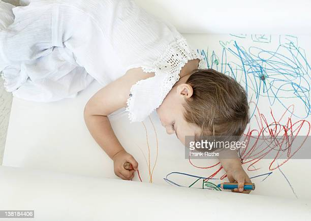 a young kid at the floor while drawing