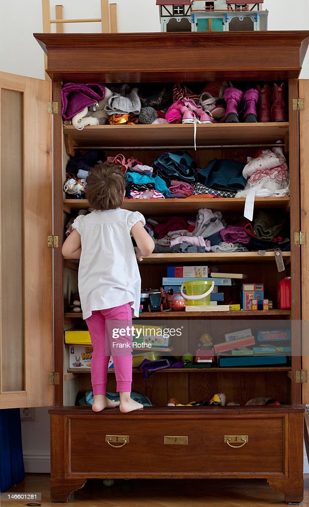 a young kid in front of here closet searching : Stock Photo