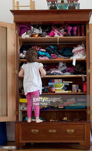 a young kid in front of here closet searching - solo una bambina femmina foto e immagini stock