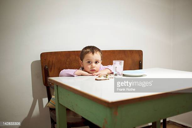 a young kid sits at a table with here food - hungry stock pictures, royalty-free photos & images