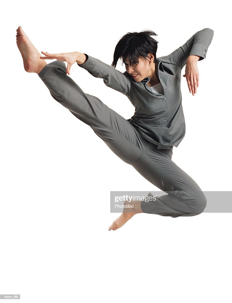 a young latin female dancer in a grey outfit jumps into the air and kicks in a karate type pose : Foto de stock