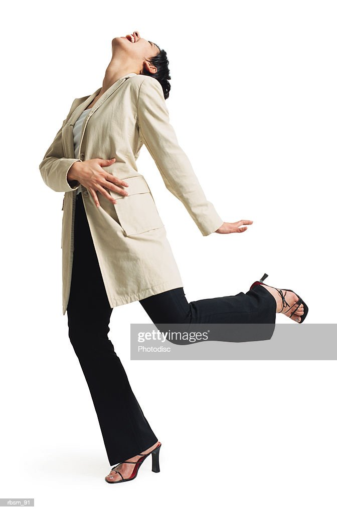 a young latin female dancer in black pants and a tan jacket stands on one foot as she tosses her head back to laugh : Foto de stock