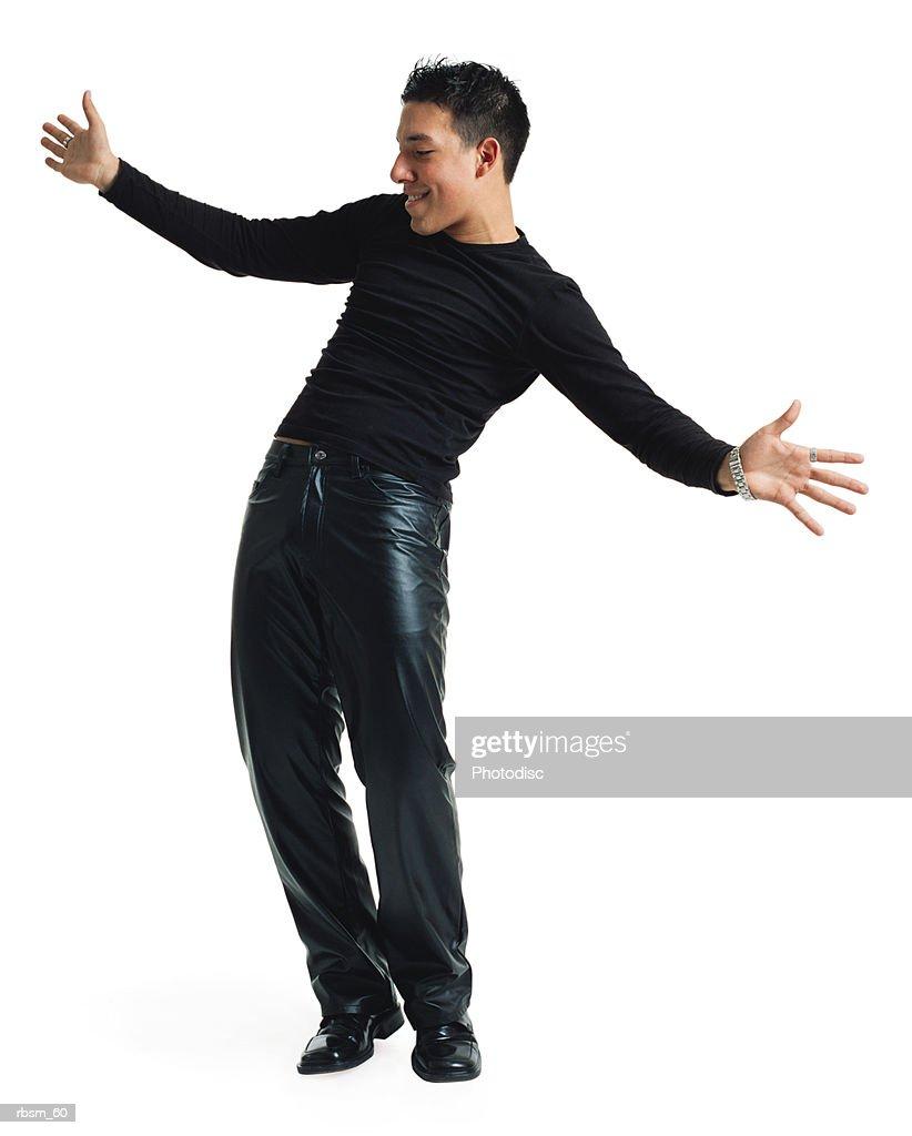 a young latin male dancer in black leather pants and a black shirt leans his body back and playfully stretches out his arms as he smiles : Foto de stock