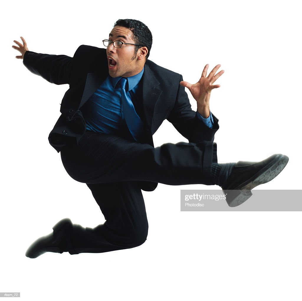 a young latin male dancer with glasses in a black business suit and blue shirt and tie jumps up and kicks wildly in the air while looking surprised : Foto de stock