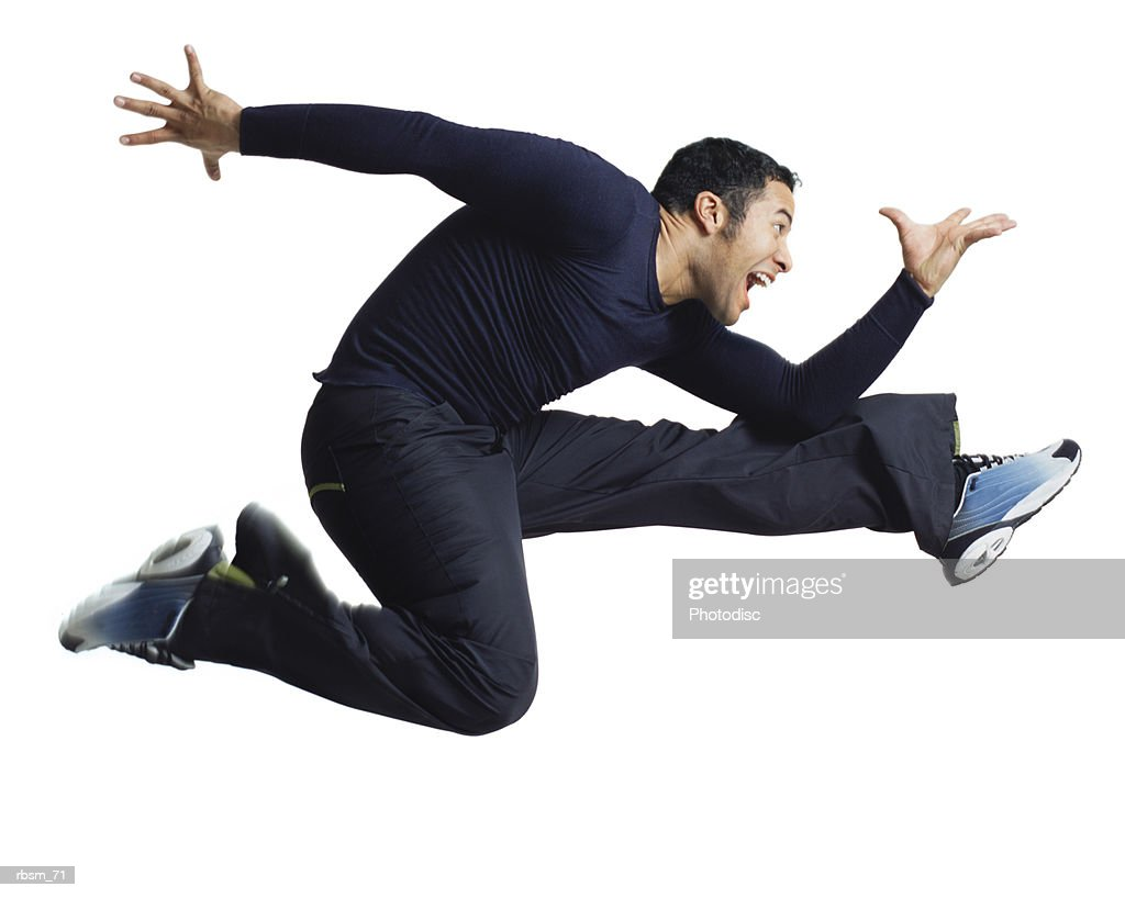 a young latin male dressed in blue jumps high and flies through the air in a running pose : Foto de stock