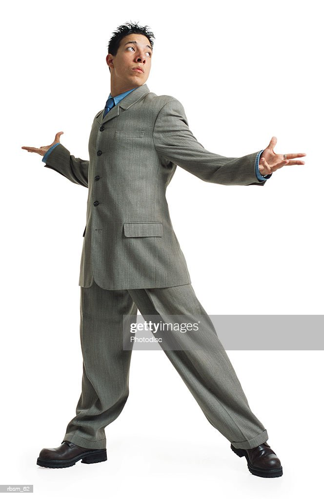 a young latin male in a grey suit and blue dress shirt turns his body and raises up his arms to show indifference : Foto de stock
